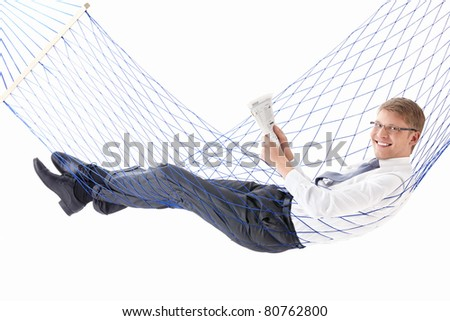 Young businessman reading a newspaper in a hammock isolated