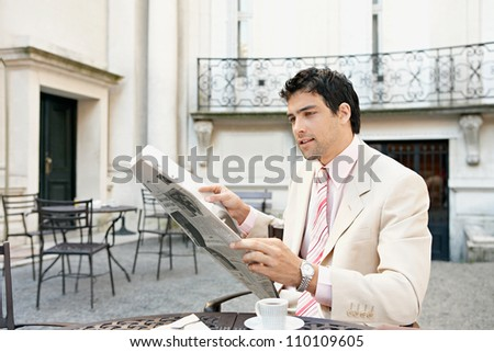 Young businessman reading a newspaper while sitting in a coffee shop's terrace table drinking coffee.
