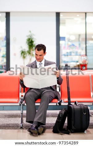 young businessman reading newspaper at airport