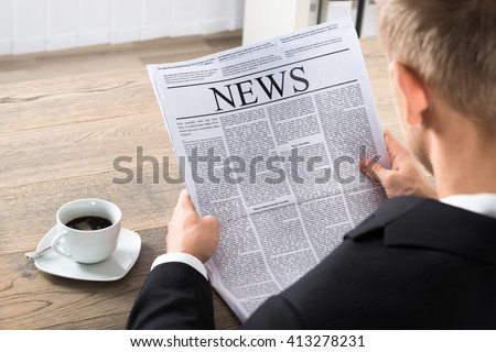 Young Businessman Reading Newspaper At Desk In Office