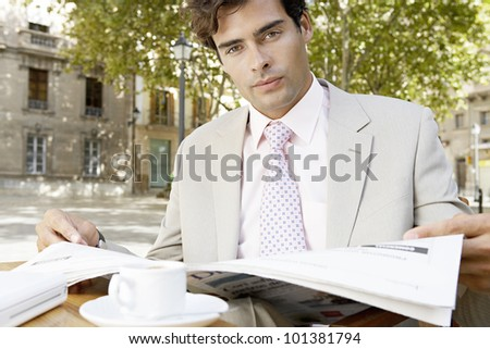 Young businessman reading the newspaper while sitting in a coffee shop's terrace in the city, outdoors.