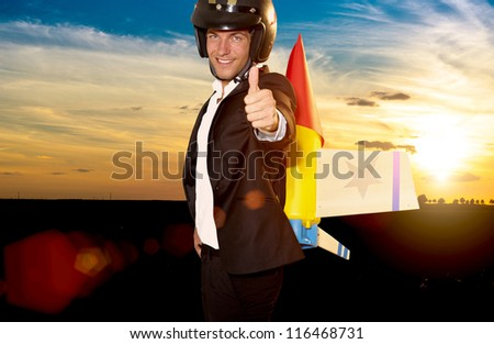 young businessman ready to climb with rocket on his back - stock photo