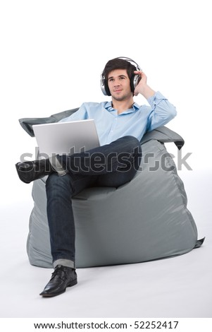 Young businessman relax with music and laptop sitting on bean bag on white background