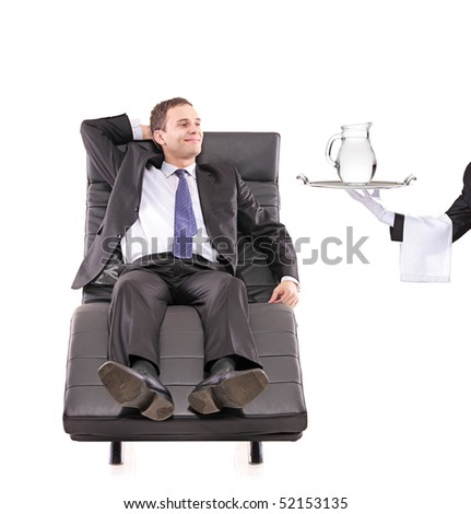 Young businessman relaxing on a sofa while the butler holding a pitcher isolated on white