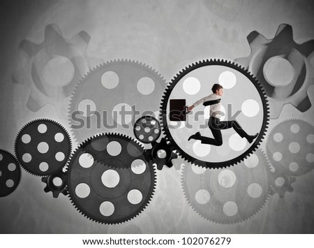 Young businessman running in a gear of a mechanism