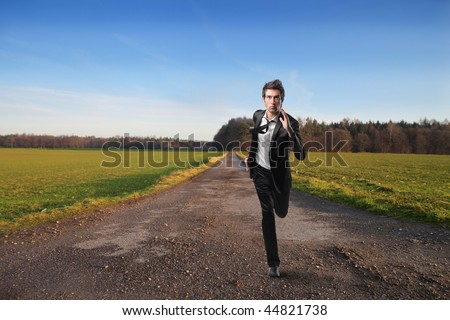 young businessman running on country road