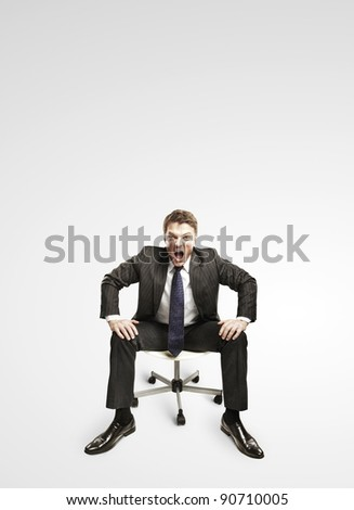 Young businessman shouting and sitting on a chair. On a gray background