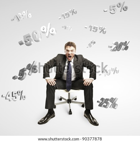 Young businessman shouting and sitting on a chair under falling percents signs. Discount concept depicting percentage symbols falling on man. On a gray background