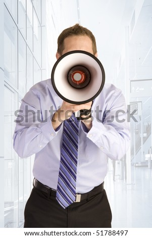 Young businessman shouting into a megaphone.