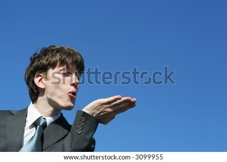 young businessman showing something or blowing on his hand