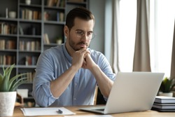Young businessman sit at home office desk looks at laptop read media news online, learn new e app, analyzing project, stuck with challenge business task, thinks over problem, search solution concept