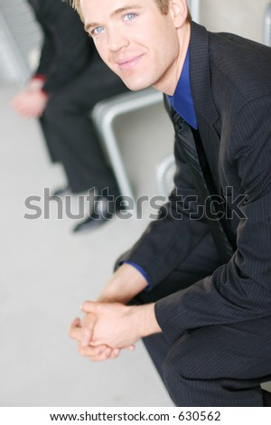 Young businessman sits on bench with a smile