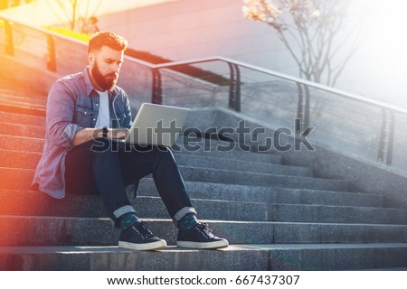 Young businessman sits outdoor on steps, using laptop and looks on his screen.Hipster bearded man is working,blogging,chatting online,checking email.Student learning online.Social network.Lifestyle #667437307