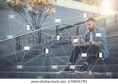 Young businessman sits outdoor on steps, using laptop.Blockchain technology. Trading on stock exchange. Hipster bearded man is working, learning online.Education for adults.Social network.Film effect