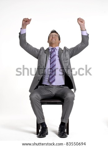 Young businessman sitting and celebrating on a chair.
