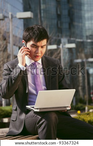Young businessman sitting and talking on mobile phone.