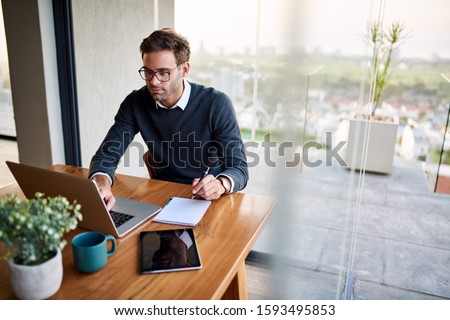 Photo of Young businessman sitting at a table at home working on a laptop and writing down ideas in a notebook