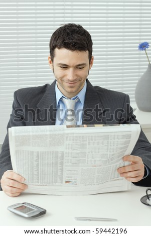 Young businessman sitting at desk and reading business news, smiling.