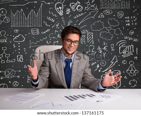 Young businessman sitting at desk with business scheme and icons