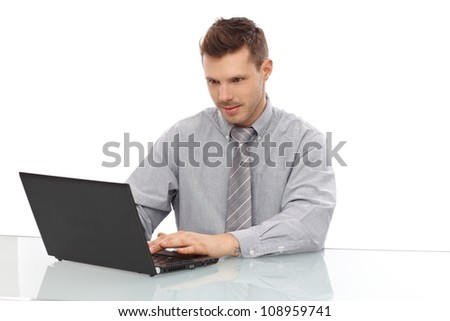 Young businessman sitting at desk, working on laptop computer.