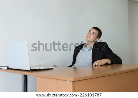 Young Businessman Sitting at His Table Area Looking Up While Thinking a Brighter Idea.
