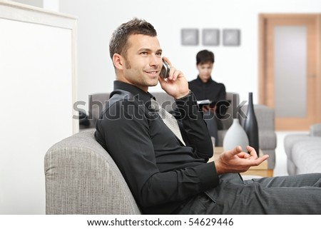 Young businessman sitting at office lobby talking on mobile phone, smiling.