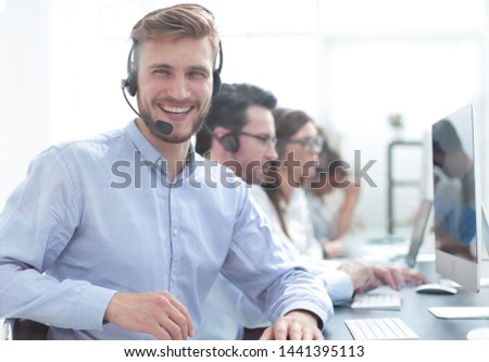 young businessman sitting at the table in the call center.