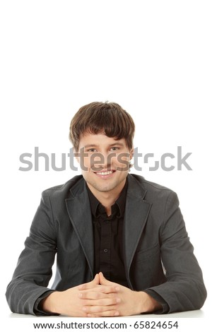 Young businessman sitting behind the desk , isolated on white