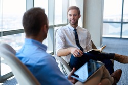 Young businessman sitting comfortably in an open modern office, smiling while having a positive conversation with a coworker