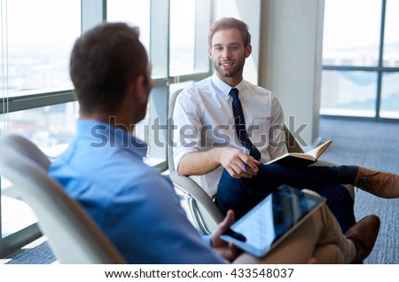 Young businessman sitting comfortably in an open modern office, smiling while having a positive conversation with a coworker #433548037