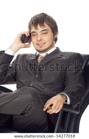 young businessman sitting in an armchair and smiling speaking on a mobile phone isolated on white