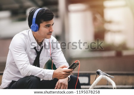 young businessman sitting in city background smile listens music with earphones