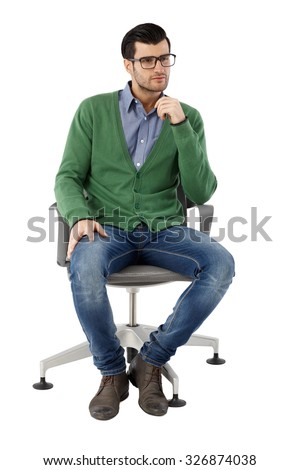 Young businessman sitting in swivel chair over white background, thinking. Full-length. #326874038