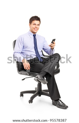 Young businessman sitting on a chair and holding a mobile phone isolated on white background
