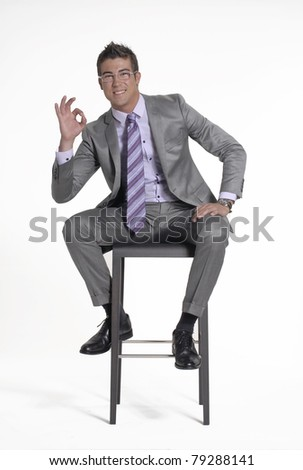 Young businessman sitting on a chair on white background.