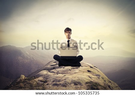 Young businessman sitting on a hill and using a laptop