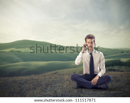 Young businessman sitting on a meadow and using a mobile phone - stock photo