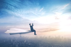 Young businessman sitting on a paper aircraft while flying above a city and looking through binoculars