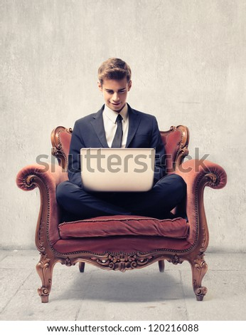 Young businessman sitting on a vintage armchair using a laptop computer