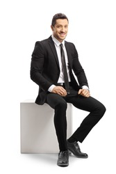 Young businessman sitting on a white cube and looking at camera isolated on white background
