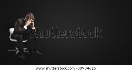 Young businessman sitting on chair with head down as if sad or depressed. On a black background.