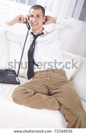 Young businessman sitting on couch talking on phone, smiling.