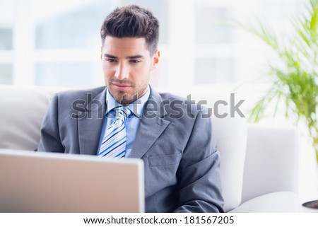 Young businessman sitting on couch using his laptop in the office
