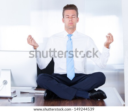 Young Businessman Sitting On Desk Practicing Yoga In Office