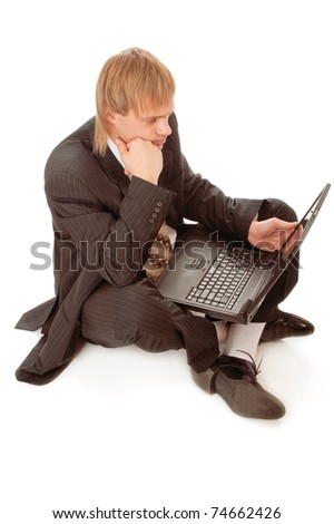 Young businessman sitting on floor with laptop isolated on white background