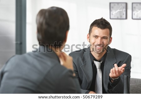 Young businessman sitting on sofa at office talking to businesswoman, smiling. #50679289