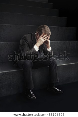 Young businessman sitting on stairs with head down as if sad or depressed.
