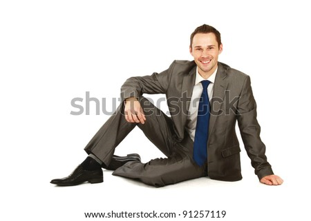 Young businessman sitting on the floor, isolated on white background