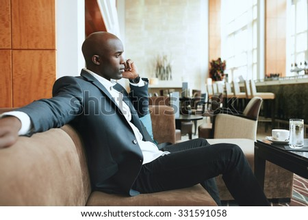 Young businessman sitting relaxed on sofa at hotel lobby making a phone call, waiting for someone.