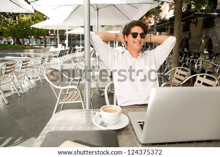 Young businessman sitting with his arms behind his head at a coffee shop while smiling with his laptop computer, outdoors.